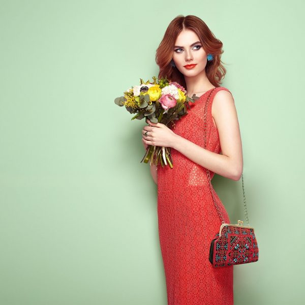 Blonde young woman in elegant red dress with Persian Balochi embroidery crossbody bag