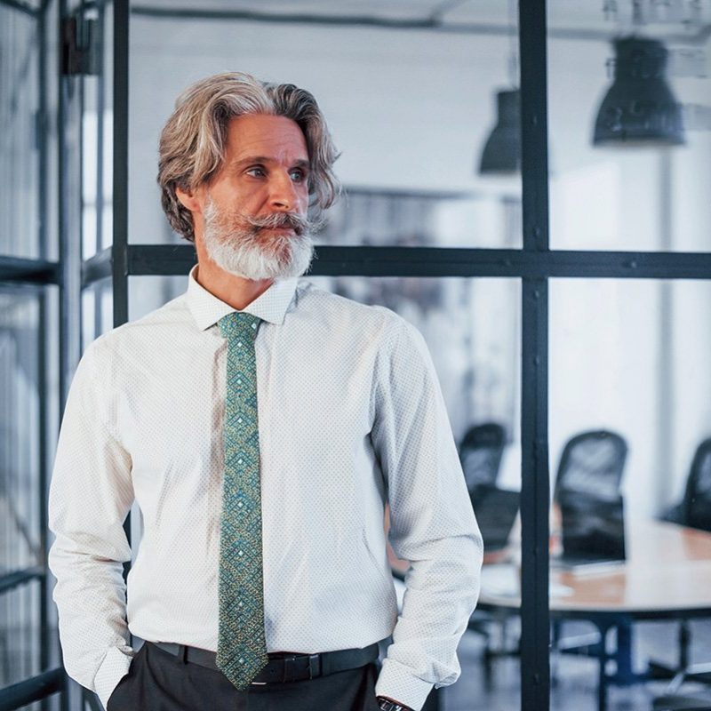 Mature businessman with grey hair and beard in formal clothes is in the office Balochi embroidery tie