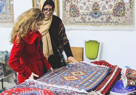 A Persian Woman Shows An Authentic Caltural Persian Carpet To Western Girl In Persian Heritage Carpet Exhibition.