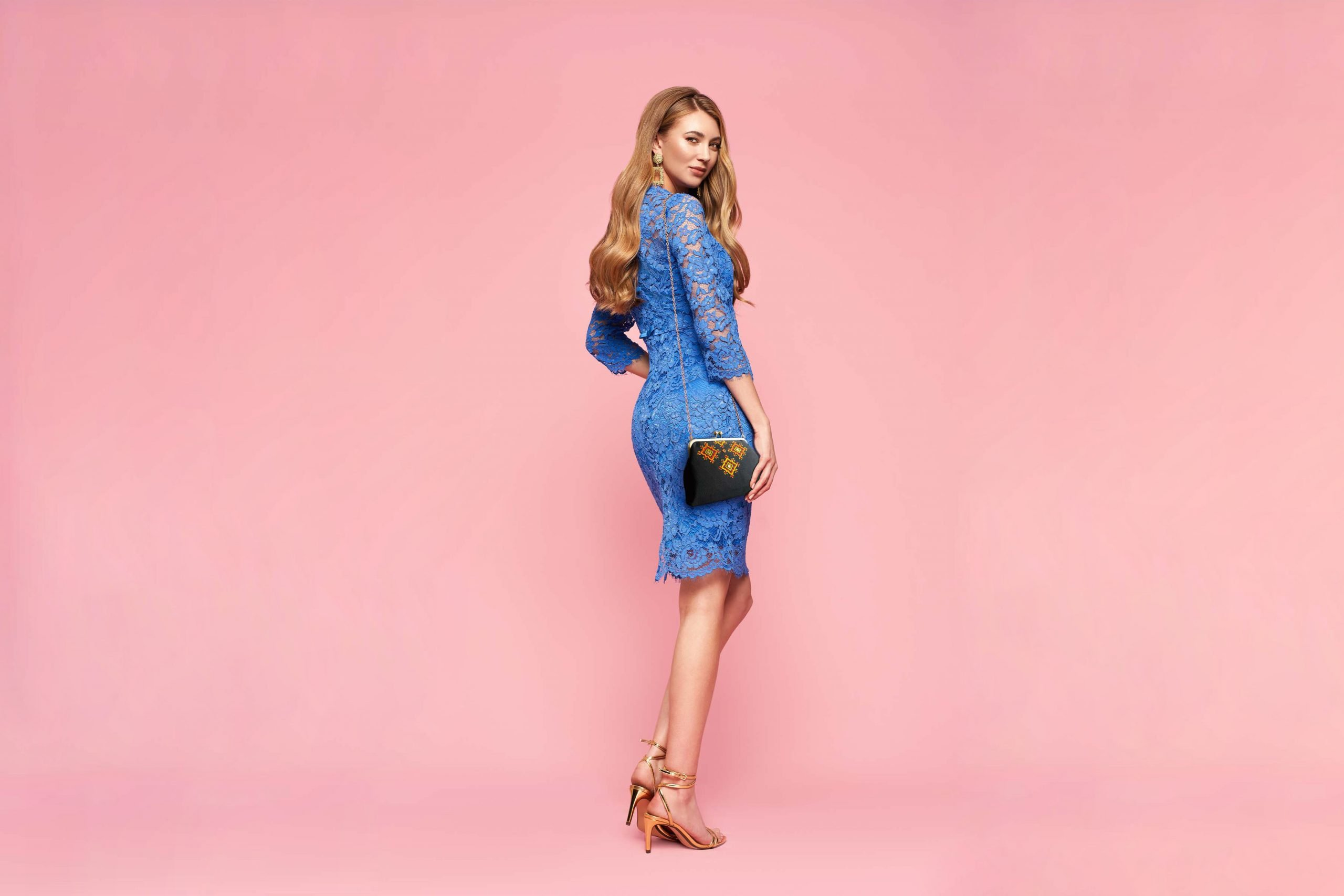 Blonde young woman in elegant blue dress wiith Persian Balochi embroidery crossbody bag