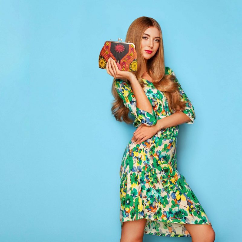 Blonde young woman in floral spring summer dress with Persian Balochi embroidery crossbody bag