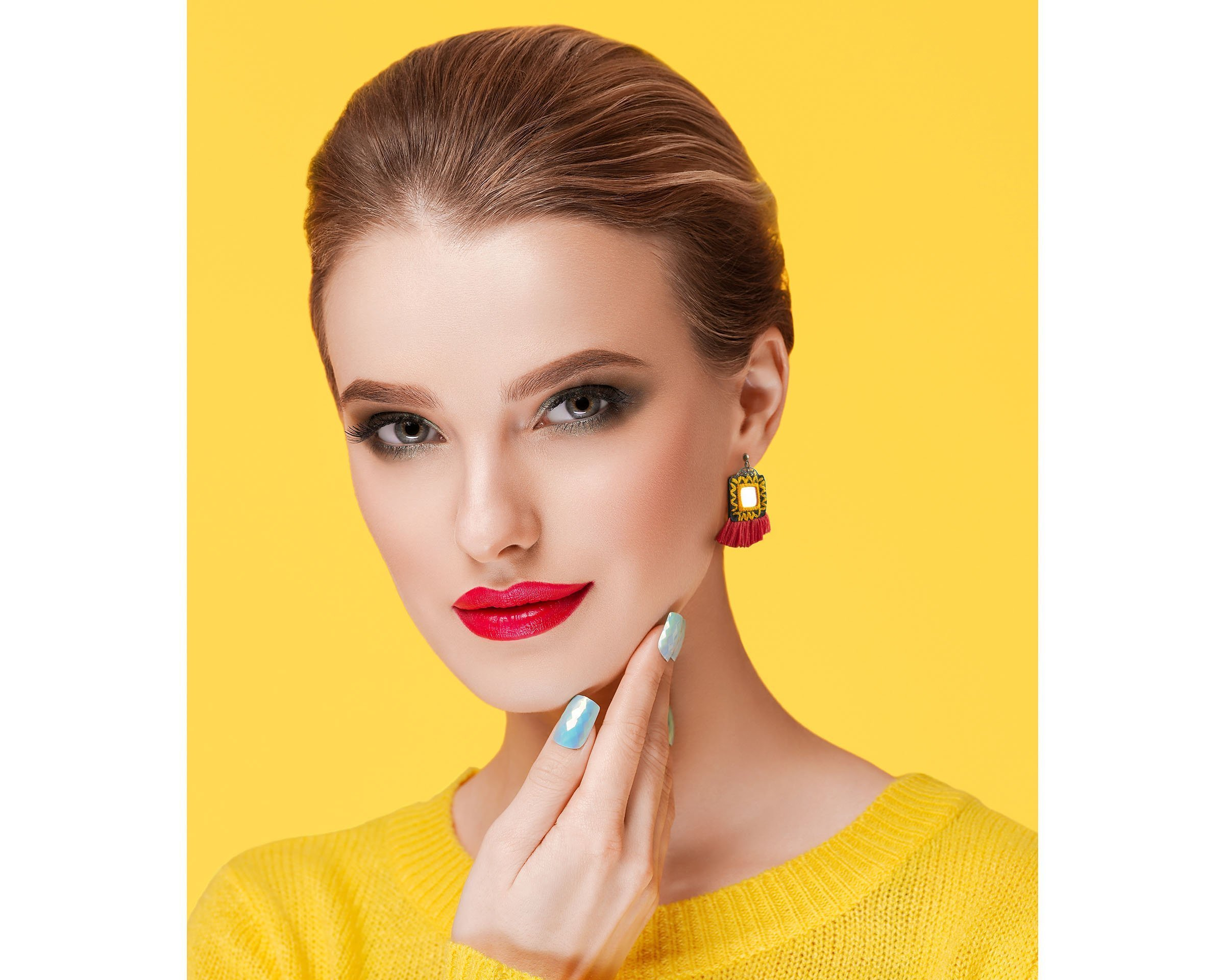 Colorful makeup woman in yellow clothes on color summer and Persian Balochi embroidery earrings with red tassel and mirror