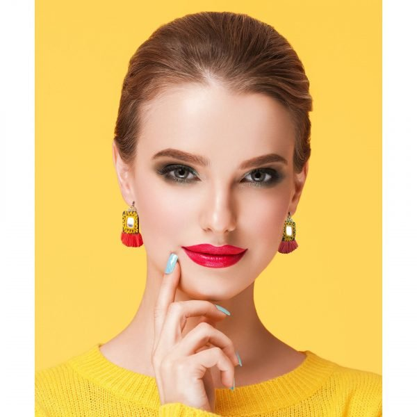 Colorful makeup woman in yellow clothes on color summer background and Persian Balochi embroidery earring red tassel and mirror
